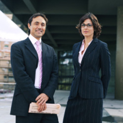 Businessman and woman standing outdoors, portrait